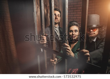 Two gentlemen and a lady behind bars in the prison. #573532975