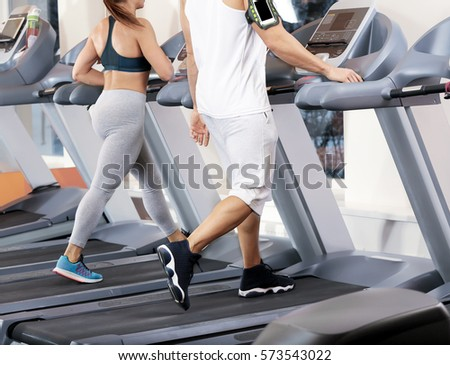 Young people running on treadmills in gym #573543022