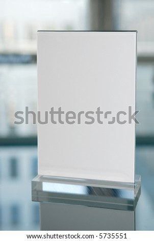 Plexiglass information board on glasstable with reflection of a business building.