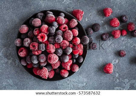 Frozen raspberry, blueberry, cranberry on black background. Frozen fruit. Top view, flat lay, close up. Royalty-Free Stock Photo #573587632
