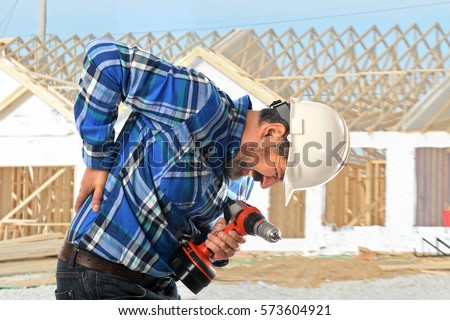 Hispanic worker getting back injury on construction site #573604921