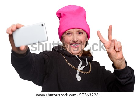 Funny granny makes a selfie. A white smartphone in one hand and other hand shows a peace sign. Nonchalant pensioner shares her uplifted mood through a social media post.