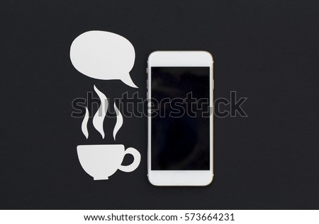 White phone and cartoon text bubble and hot drink cup. Breakfast with smartphone flat lay photo. Speaking cellphone banner template with text place. Black screen phone with speech bubble and tea cup
