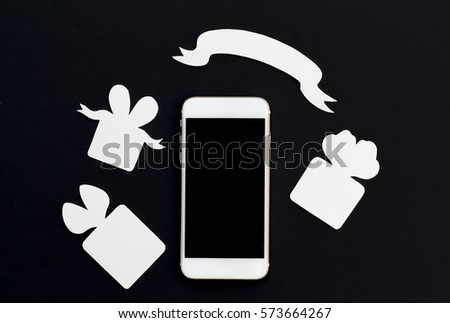 White phone with gift boxes and blank ribbon banner on black background. Black and white smartphone and paper cut presents. Black screen cellphone flat lay. Discount or sale event banner template