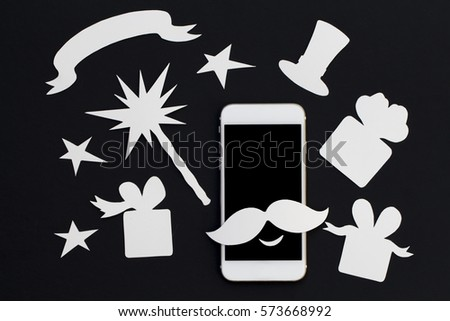 White phone in paper cut collage with magic wand and presents. Smartphone magician with mustache and vintage hat. White phone magical show banner template with text place. Smiling phone flat lay photo