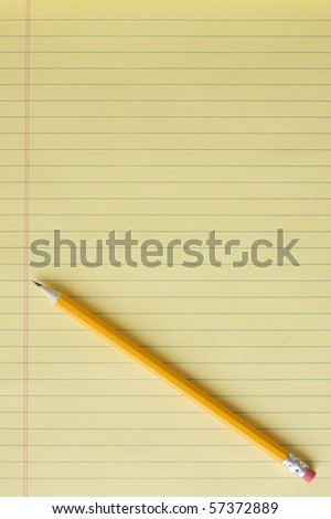 Blank yellow lined legal pad with yellow number 2 pencil placed at a diagonal.  Portrait orientation. #57372889