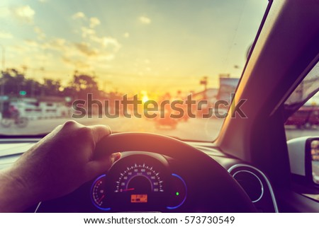 image of people driving car on day time for background usage .(take photo from inside focus on driver hand) #573730549