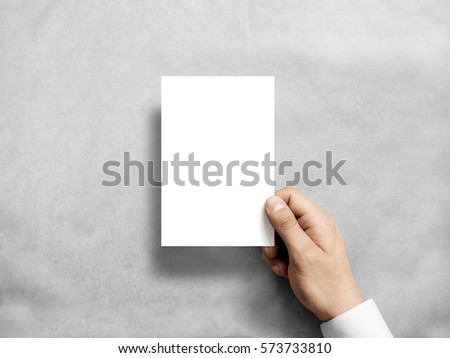 Hand holding blank white vertical postcard flyer mockup. 6 x 4 leaflet mock up presentation. Postal holder. Man show clear post card paper. Sheet template. Invitation booklet reading first person view #573733810