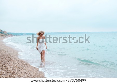beautiful young blonde woman walking on the beach near the sea in a white dress #573750499