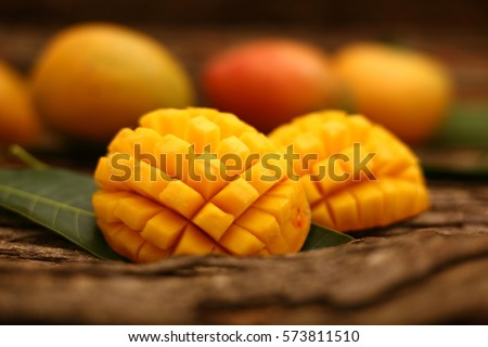 Famous Alphonso mango slices over wood  background,Selective focus image. #573811510