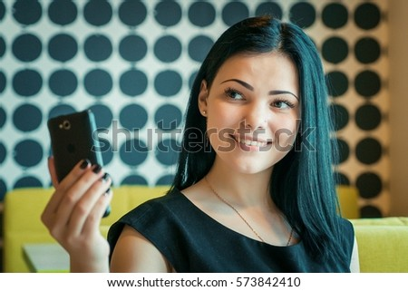 Young attractive model girl aged 20s making selfie photo using a smartphone indoors #573842410