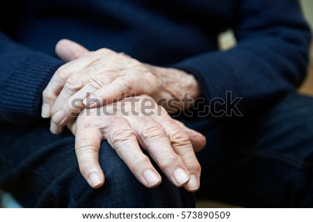 Close Up Of Senior Man Suffering With Parkinsons Diesease #573890509