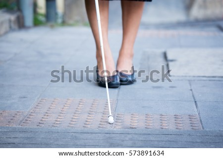Blind woman is walking on the sidewalk, using a white cane. #573891634