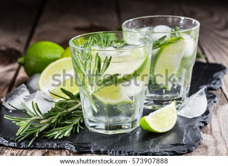 drink with fresh lime and rosemary on a wooden background #573907888