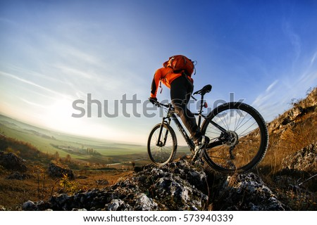back view of a man with a bicycle and red backpack against the blue sky. cyclist rides a bicycle. Rear view people collection. backside view of person. blue sky background and mound. Royalty-Free Stock Photo #573940339