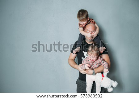 stressed young dad with two small children in his arms Royalty-Free Stock Photo #573960502