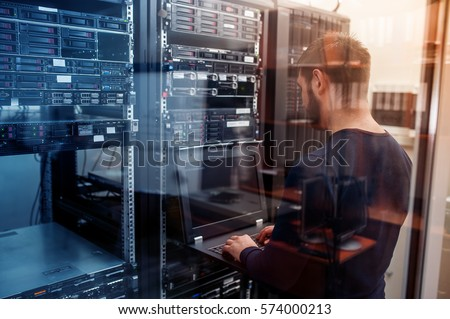 young it engeneer business man with thin modern aluminium laptop in network server room Royalty-Free Stock Photo #574000213