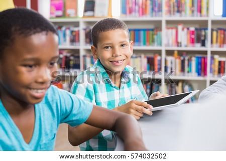 Kids using digital tablet in library at school #574032502