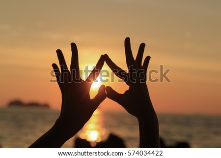 Hands in the shape of heart silhouette at sunset for love concept, Valentines background. #574034422
