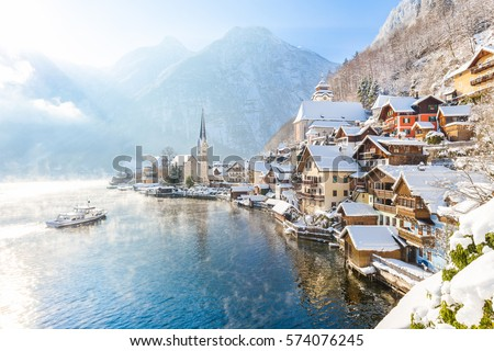 Classic postcard view of famous Hallstatt lakeside town in the Alps with traditional passenger ship on a beautiful cold sunny day with blue sky and clouds in winter, Salzkammergut region, Austria #574076245