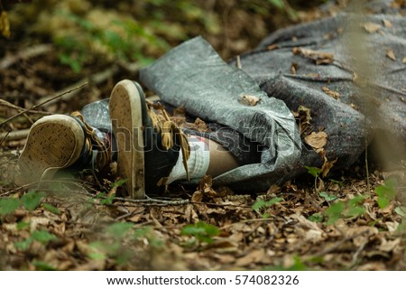 Close up view of legs of dead body wrapped in plastic fabric thrown in woods covered with leaves Royalty-Free Stock Photo #574082326