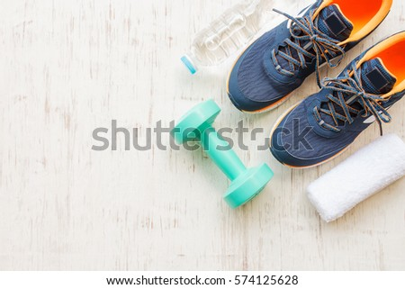 Blue running shoes with fitness accessories on white wooden background Royalty-Free Stock Photo #574125628