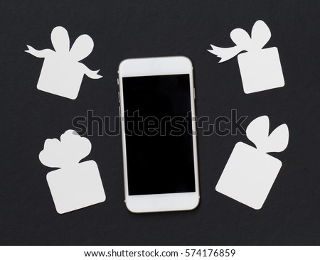 White phone with gift boxes on black background. Black and white banner template with smartphone and paper cut presents. Black screen cellphone flat lay. Holiday greeting or sale event advertisement