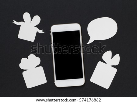White phone with text bubble and gift box on black background. Black and white banner template with text place. Smartphone and present. Black screen cellphone flat lay. Holiday greeting paper cut card
