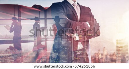superhero businessman looking at city skyline at sunset. the concept of success, leadership and victory in business. Royalty-Free Stock Photo #574251856