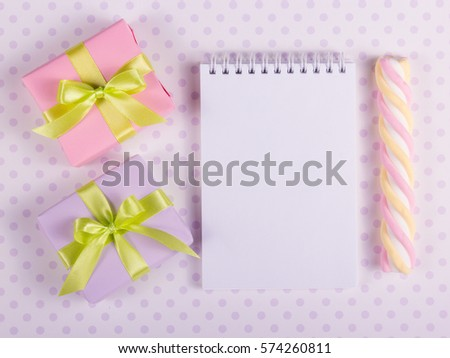Two little gift boxes with green ribbons and open notebook with a blank page. Copy space #574260811