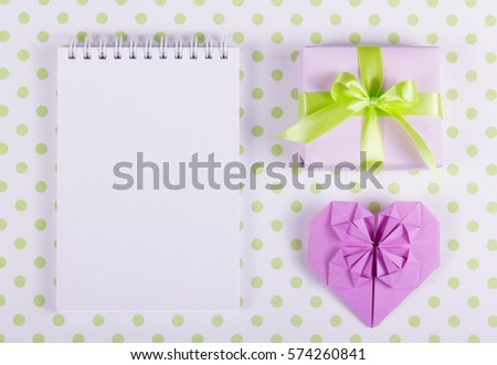 Open notebook, heart origami and marshmallow stick on a background of polka dots. St. Valentine's Day. Copy space. #574260841