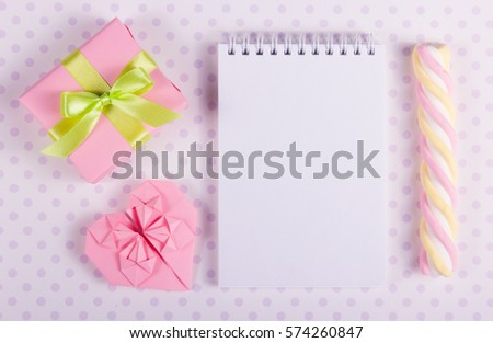 Open notebook with a blank page, Valentine origami and marshmallow stick on a background of polka dots. Copy space #574260847