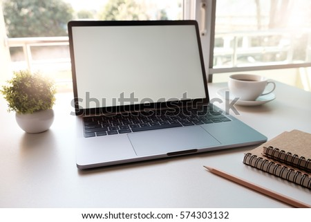 Side view laptop with blank screen on table with red cup and note book, Online shopping concept.