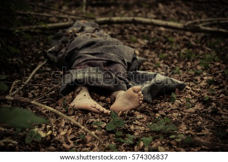 Dead body of a barefoot Caucasian boy wrapped in a blanket and abandoned on the ground in the forest Royalty-Free Stock Photo #574306837