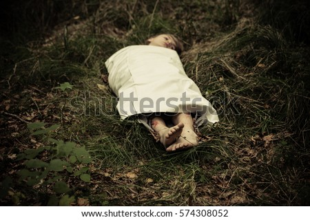 Dead boy abandoned in countryside under sheet with face visible and bare feet Royalty-Free Stock Photo #574308052