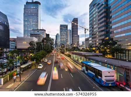 Traffic rushes in Jakarta business district along the city main avenue Jalan Thamrin at sunset in Indonesia capital city. The Transjakarta bus system enjoys its own traffic lane to avoid congestion. Royalty-Free Stock Photo #574326955