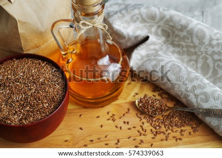 Flax seeds on spoon and in wooden bowl. Linseed oil in glass jug on wooden cutting board #574339063