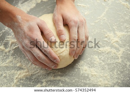 Male hands kneading dough on sprinkled with flour table, closeup #574352494