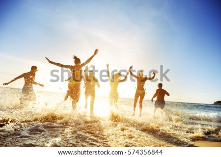 Crowd of people or friends runs to sunset sea. Beach holidays travel concept #574356844