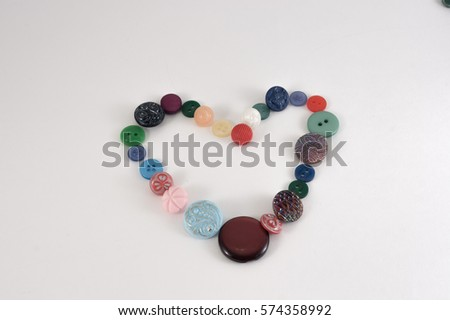 Valentine Heart of color buttons. Various sewing buttons set on white background. #574358992