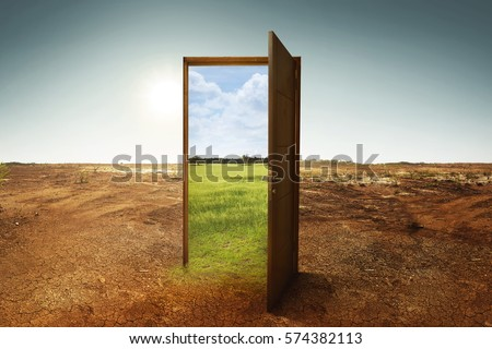 Open wooden door to the new world with green environment. Climate change concept. Royalty-Free Stock Photo #574382113