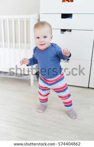 Little baby 10 months taking its first steps at home #574404862