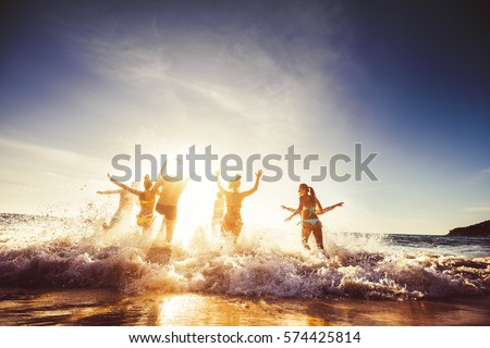 Big group of friends runs in sun light at the beach into the sea. Travel concept. Space for text #574425814