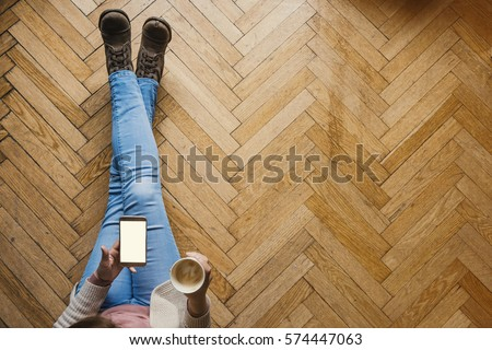 Girl with a smart phone having a coffee ona wooden floor