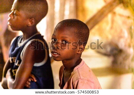 LOME, TOGO - Jan 9, 2017: Unidentified Togolese young boy in the local shaman's house. Togo children suffer of poverty due to the bad economy #574500853