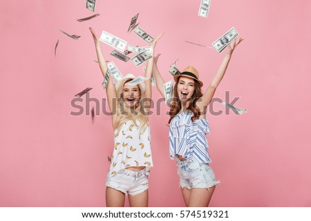 Image of two happy emotional women standing isolated over pink background holding money. #574519321