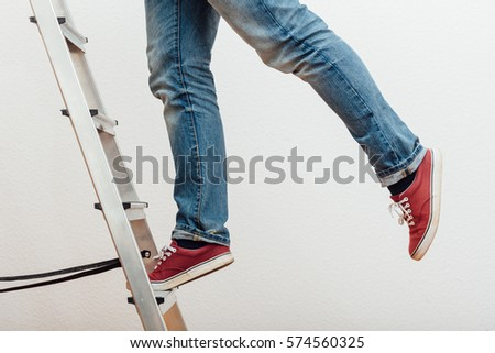 Anonymous man reaching on top of ladder climbing, indoors studio people shot. #574560325