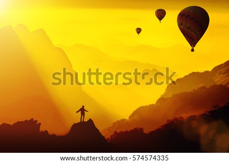 Silhouette of young traveler standing on top of mountain with amazing Fantasy sunset with hot air balloons.Travel Lifestyle success concept,adventure active vacation outdoor,happiness freedom emotion. #574574335
