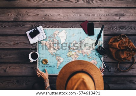 Young woman planning vacation using world map and compass along with other travel accessories. Tourist wearing brown hat looking at the world map. Royalty-Free Stock Photo #574613491