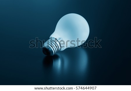 Incandescent soft white light bulb lying on a matte surface, turquoise background, close up #574644907